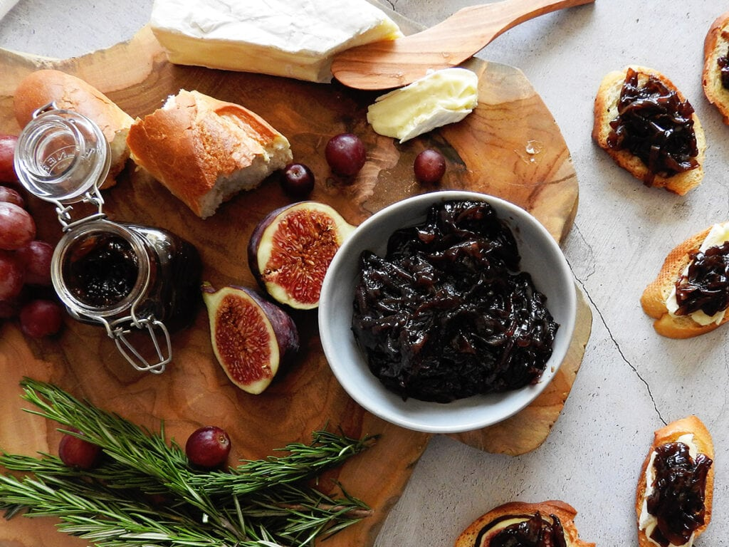 Red onion marmalade on a wooden board with bread, figs and brie