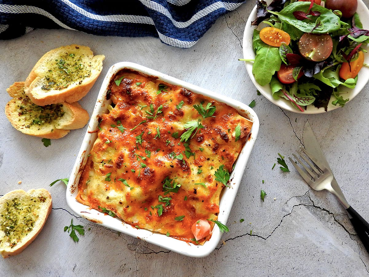 chicken lasagna cooked in a baking tray on a table