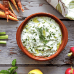 Tzatziki on a counter with carrot, radish and celery