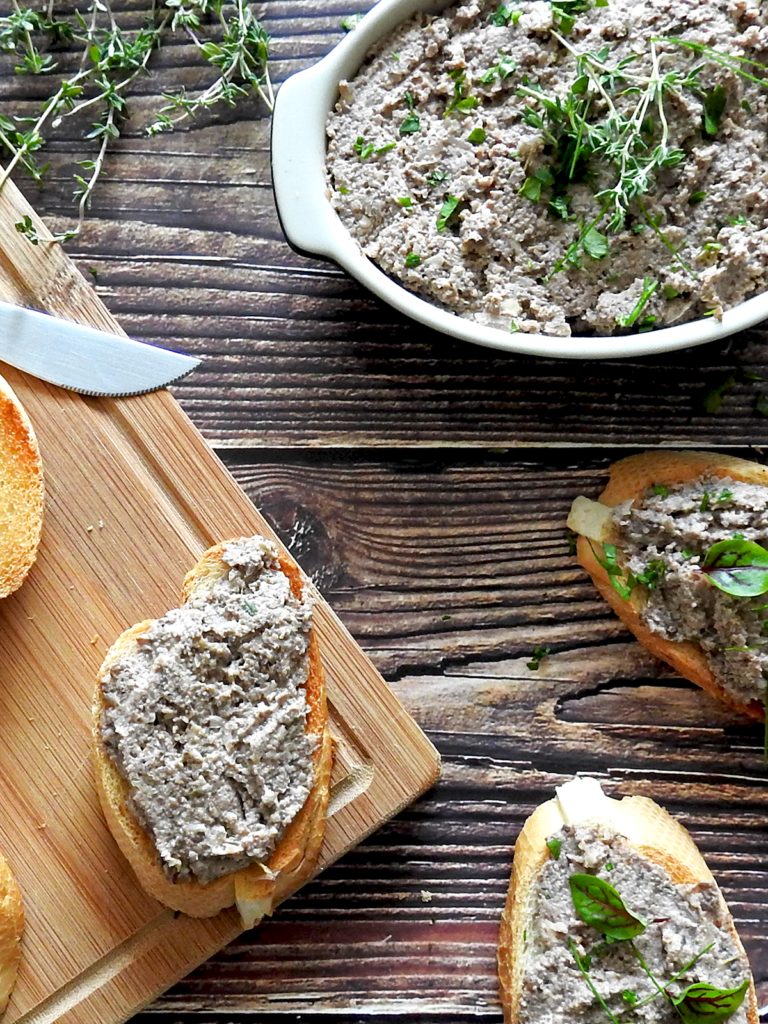 Overhead shot of mushroom pate in a bowl with sliced baguette on a chopping board