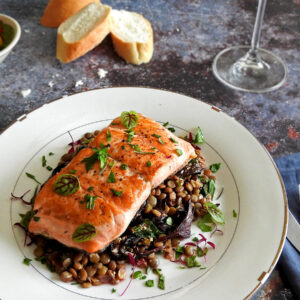 Close up of pan seared salmon on a bed of lentils