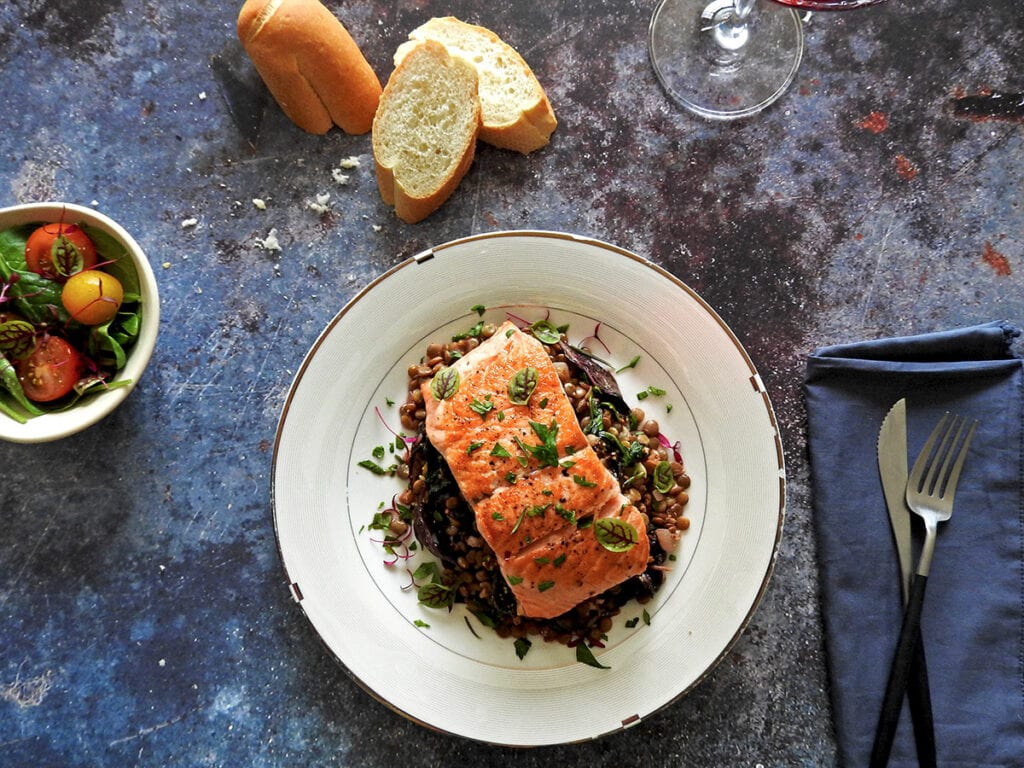 Pan seared salmon with lentils on a plate