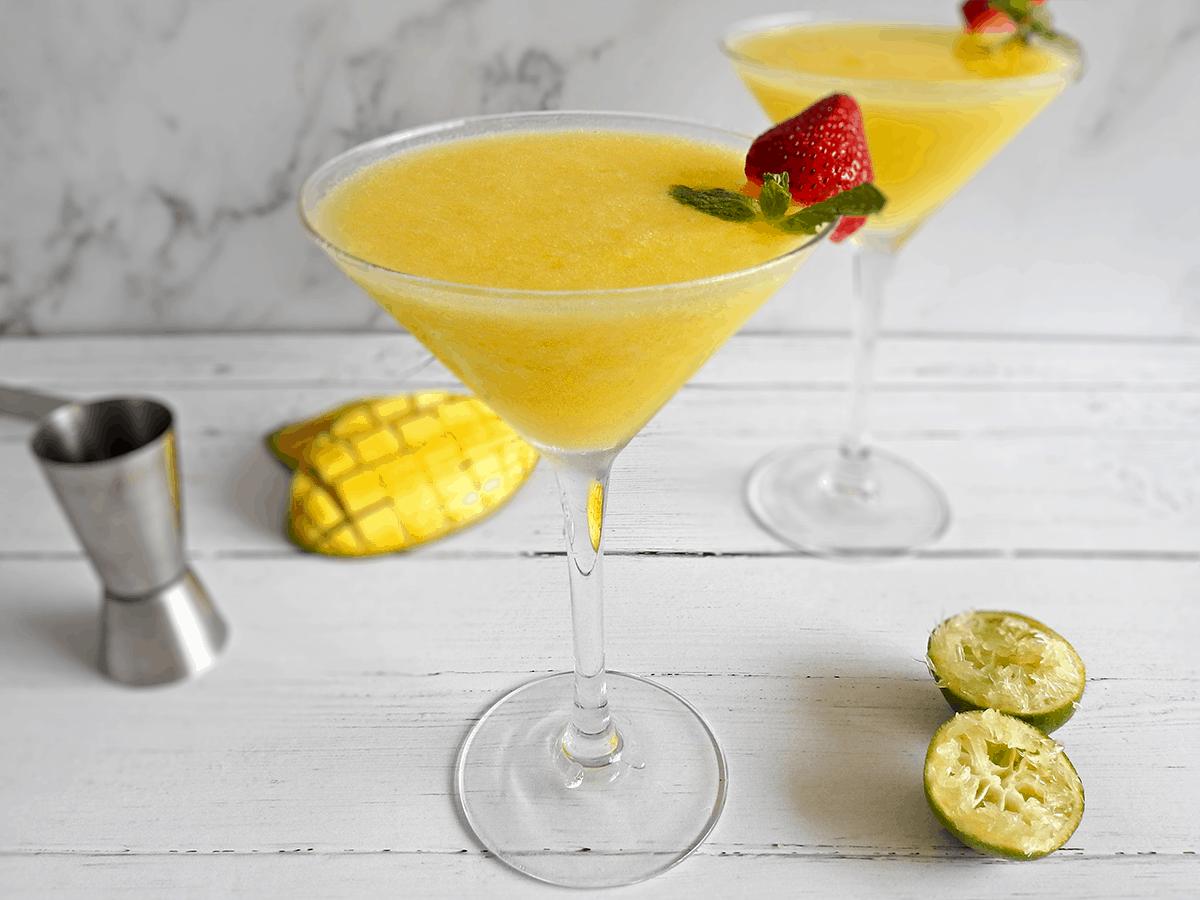 Mango daiquiris in martini glasses on a counter