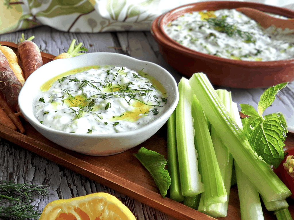 Homemade tzatziki on a board with vegetables