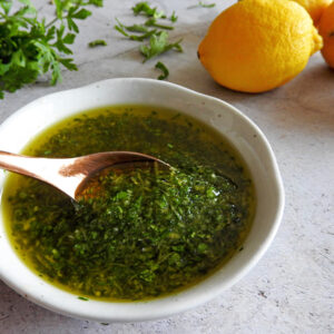 Spoon dipping into a bowl of gremolata