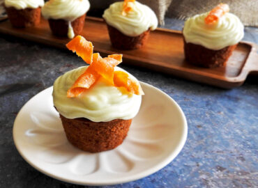 Individual carrot cake in focus with other cakes in the background