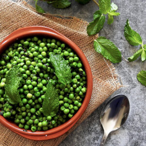 Minted peas in a bowl with mint scattered around