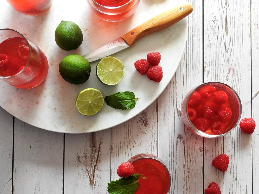 Raspberry Cordial on a Table from above with a chopping board with limes and raspberries