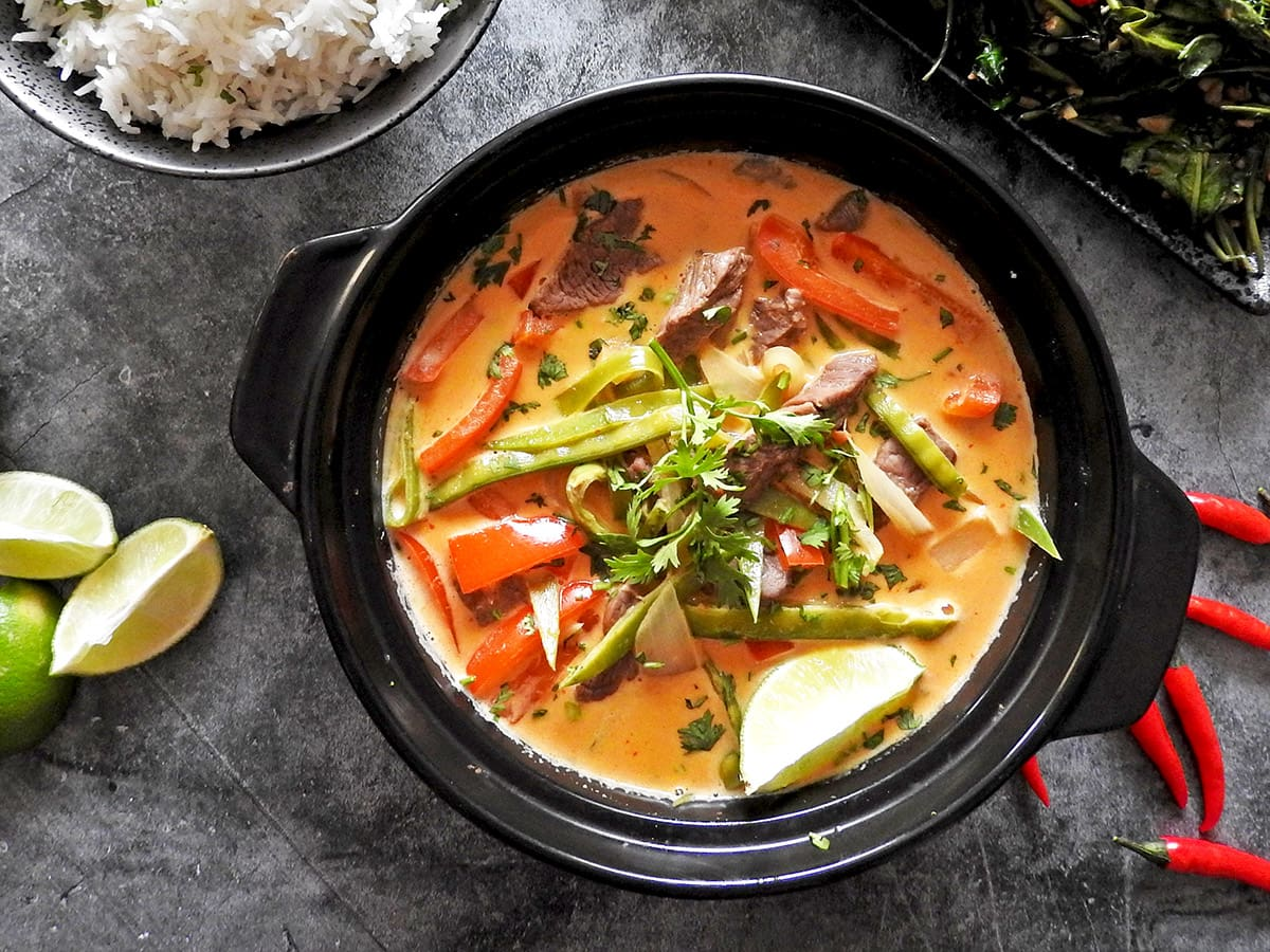 Thai red beef curry in a bowl with a bowl of rice next to it
