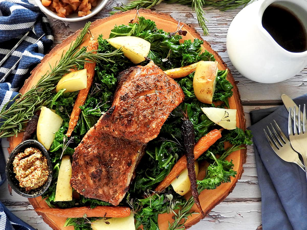 Slow cooker pork belly on a wooden platter with kale and potatoes