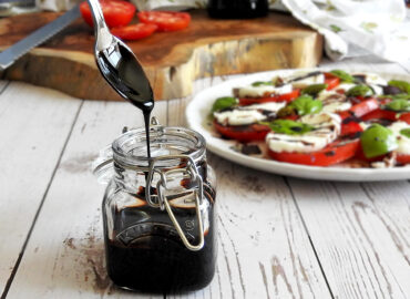 Balsamic glaze dripping off a spoon into a jar