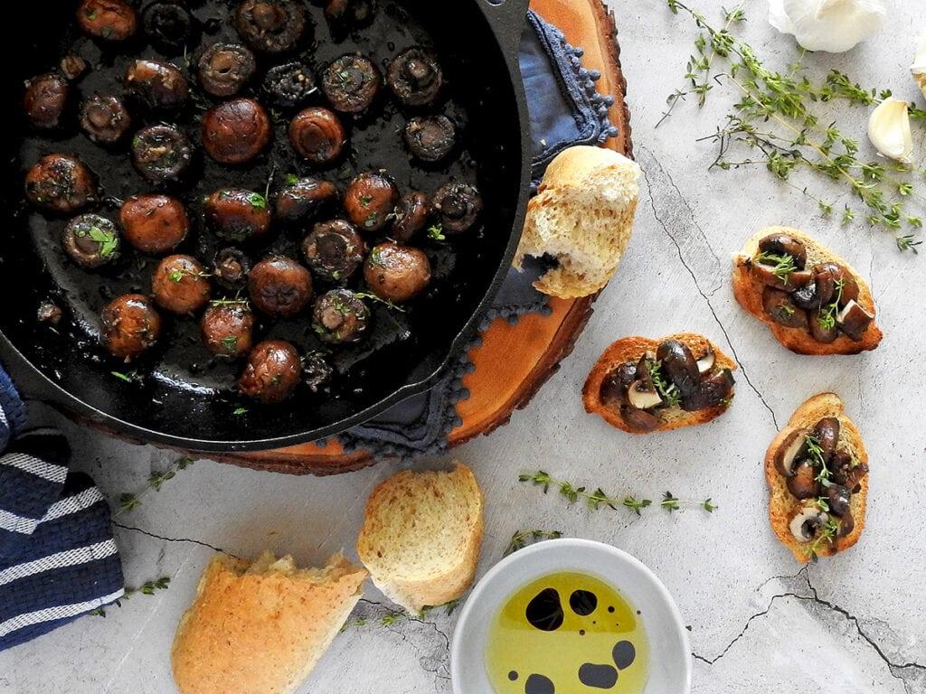 Garlic mushrooms in a pan with mushroom bruschetta next to it