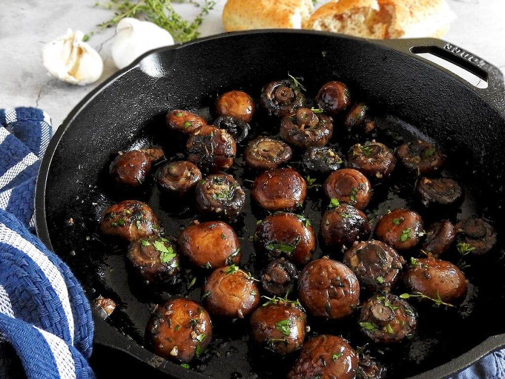Closeup of garlic mushrooms in a pan