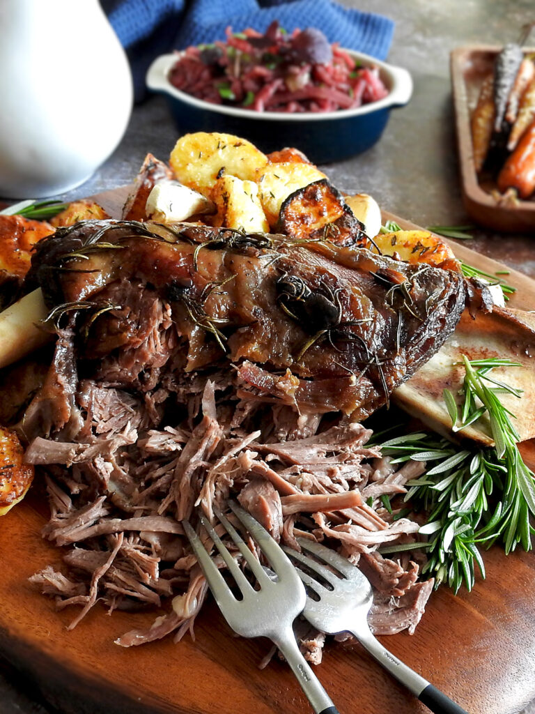 Shredded lamb shoulder on a chopping board with two forks