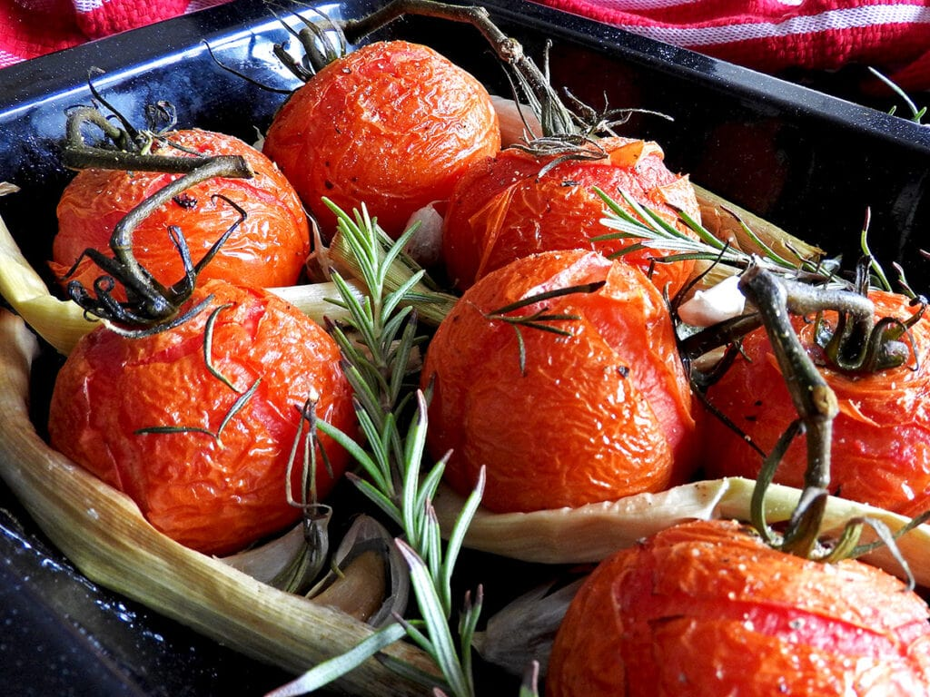 Close up of roasted leeks and tomatoes in a baking tray