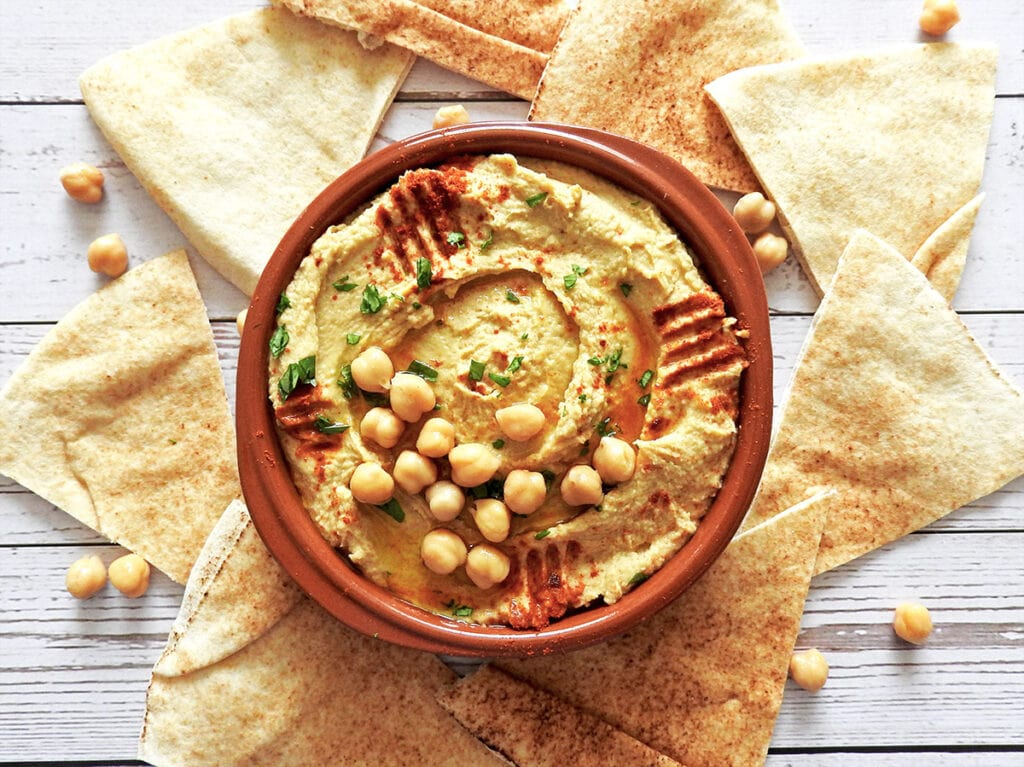 Hummus served in a bowl with pitta bread