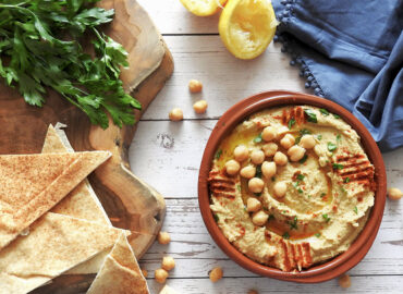 Hummus in a bowl garnished with paprika and chickpeas