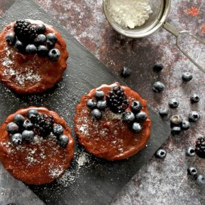 Mini Chocolate Tarts with icing sugar and berries