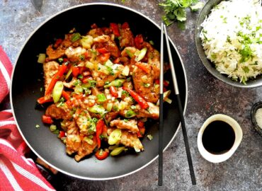 Salt and pepper chicken in a pan with rice