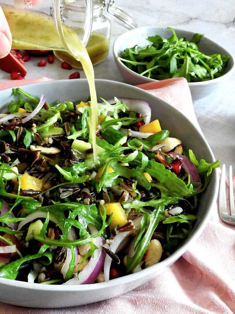 Dressing being poured onto Wild Rice Salad