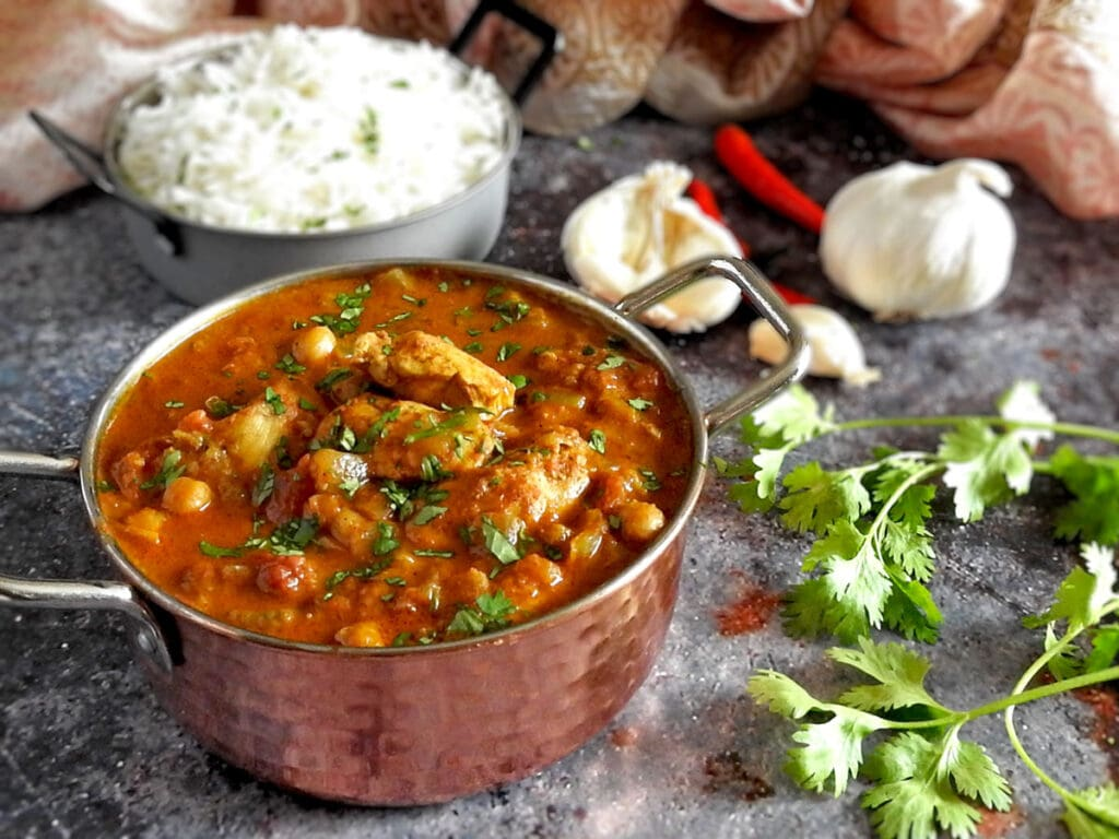 Slow Cooker Chicken Curry on a counter with garlic and coriander