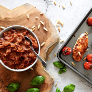 Red pesto in a bowl with a spoon