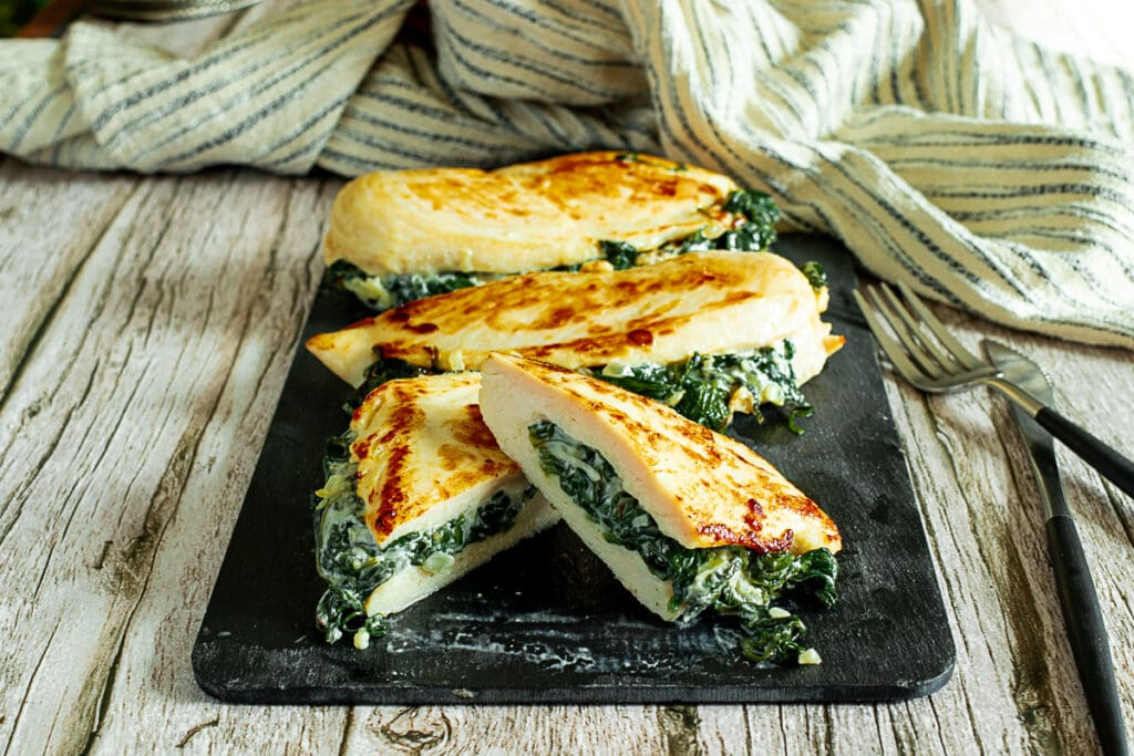 Spinach stuffed chicken breasts sliced on a board