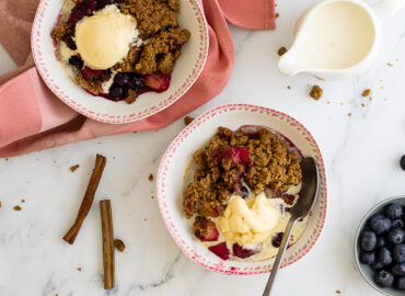 Apple and blueberry crumble in bowls with a jug of cream