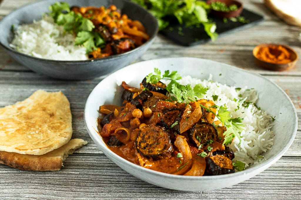 Aubergine curry in a bowl with naan