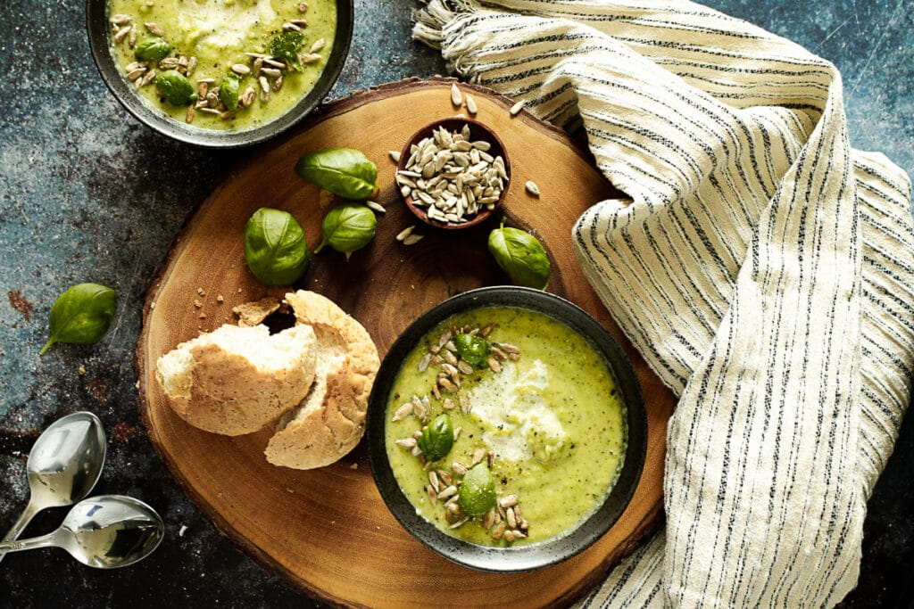 Courgette soup on a board with bread