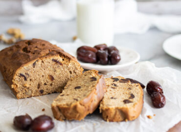Date and walnut cake sliced with dates around it