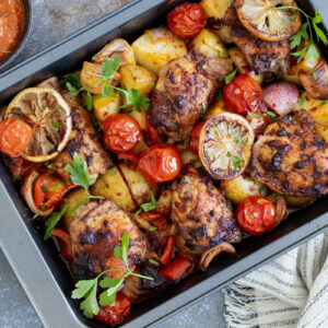 Harissa Chicken in a baking tray with a tea towel