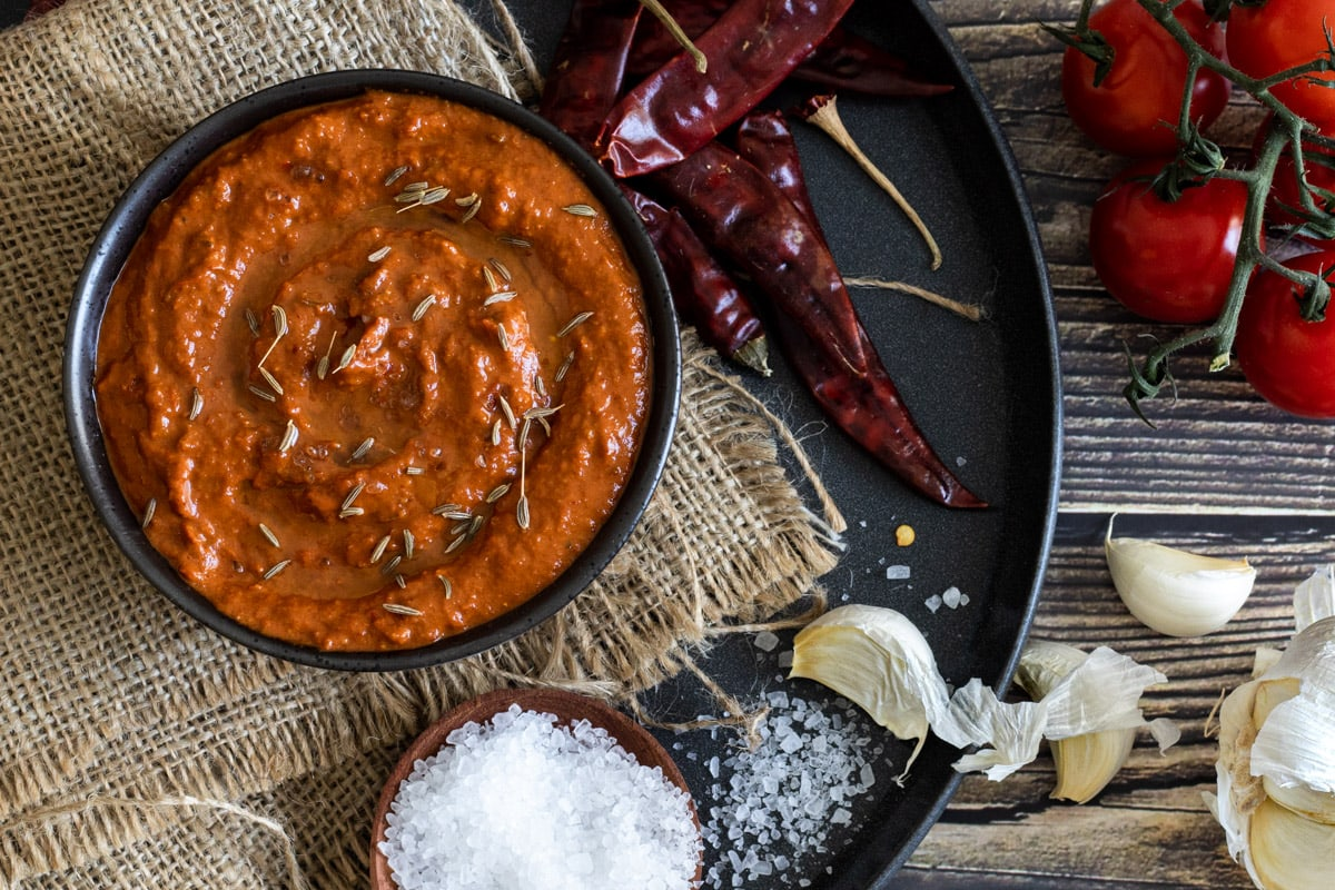 Harissa Paste in a bowl with dried chillis and salt