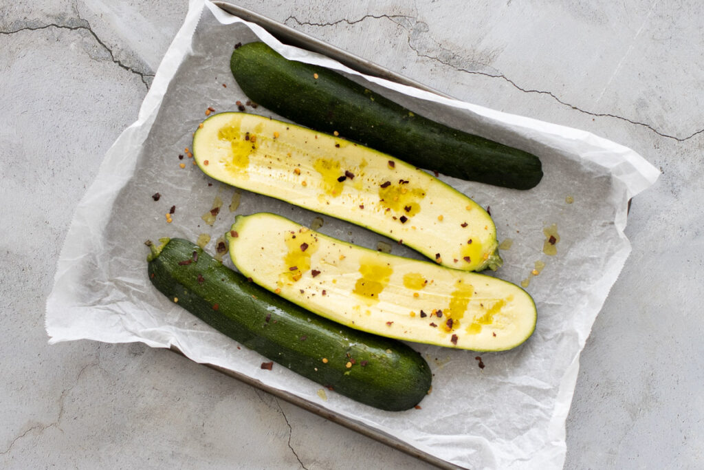 Courgettes ready for roasting on a baking tray