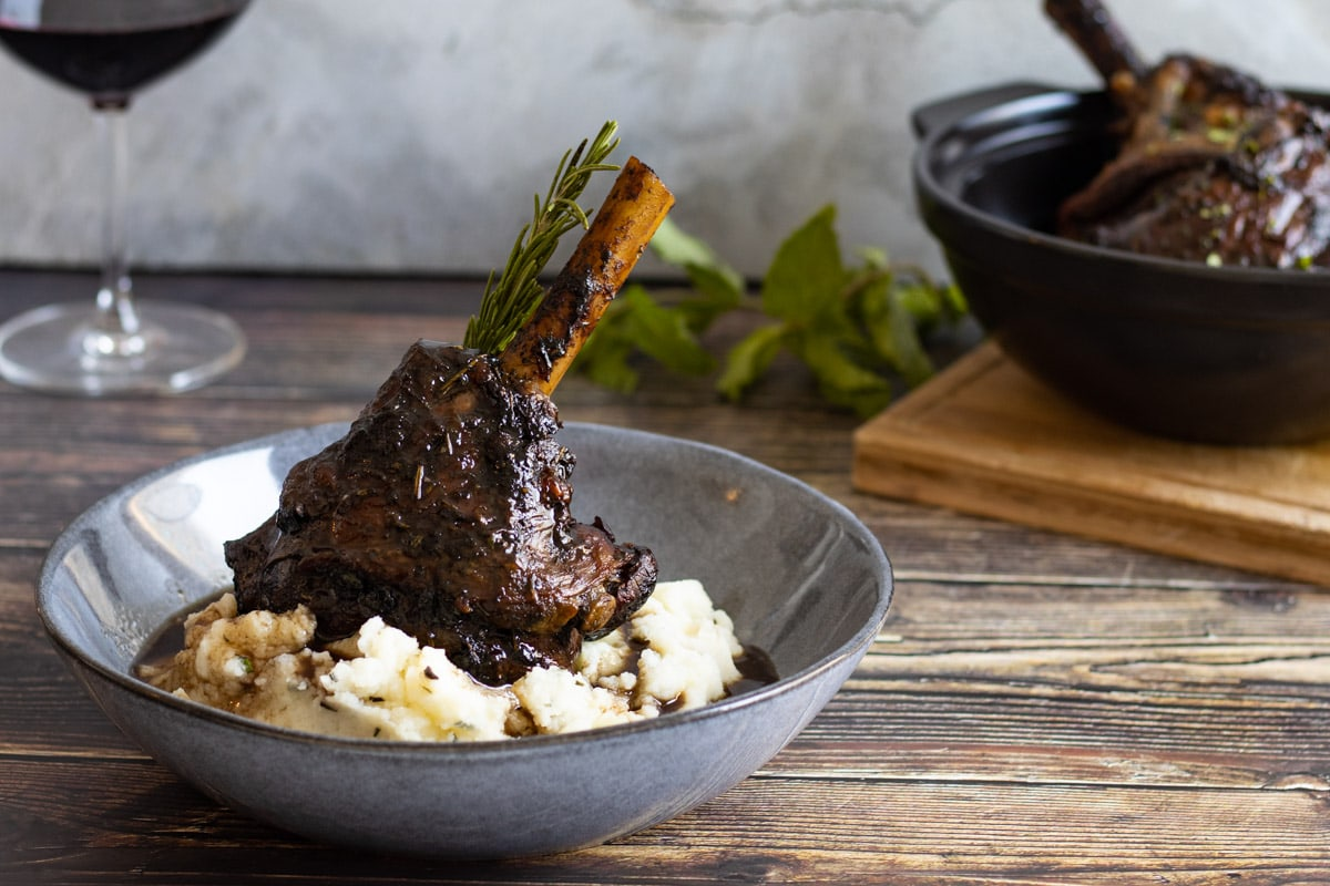 Minted lamb shank in a bowl with potato and a glass of wine
