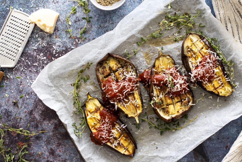 Roasted aubergine on a tray with tomato sauce and parmesan