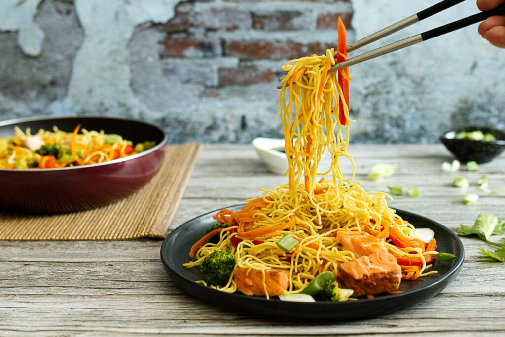 Salmon stir fry noodles being lifted with chopsticks