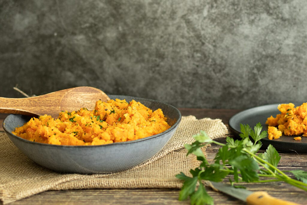 Carrot and swede mash in a bowl with a spoon and parsley