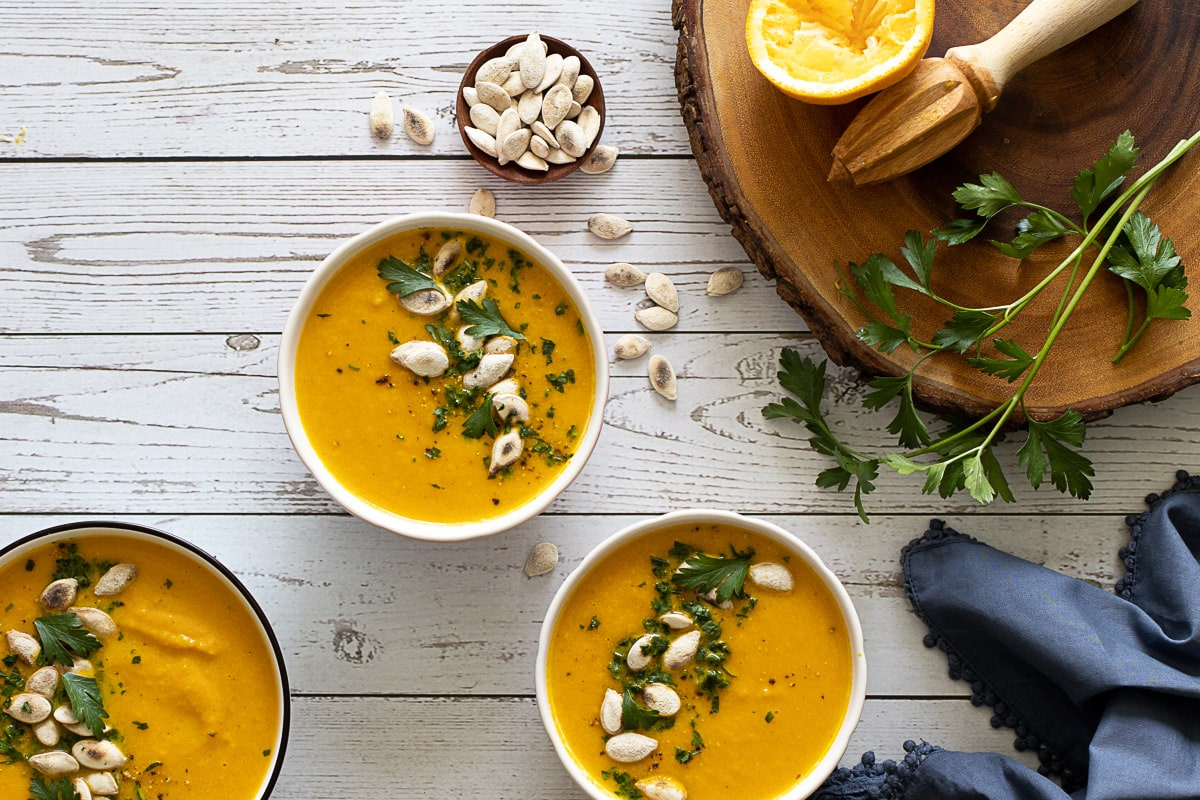 Carrot and orange soup bowls with pumpkin seeds and parsley