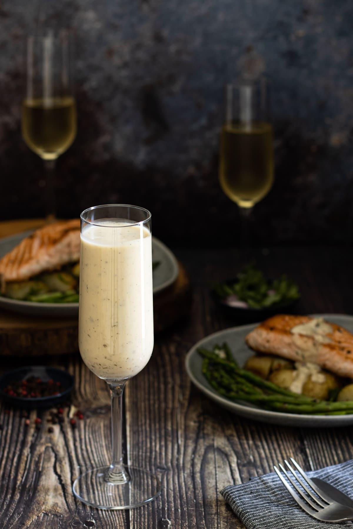 Champagne sauce in a flute with salmon in the background