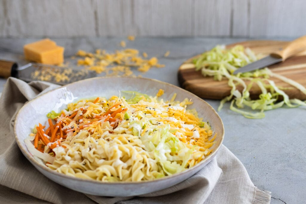 Cheese salad in a bowl with lettuce and cheese behind
