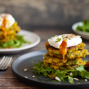 Courgette and Sweetcorn Fritters on a plate with rocket and poached egg
