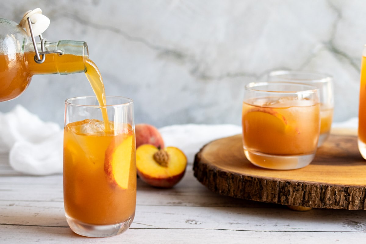 Peach iced tea being poured into a glass from a bottle