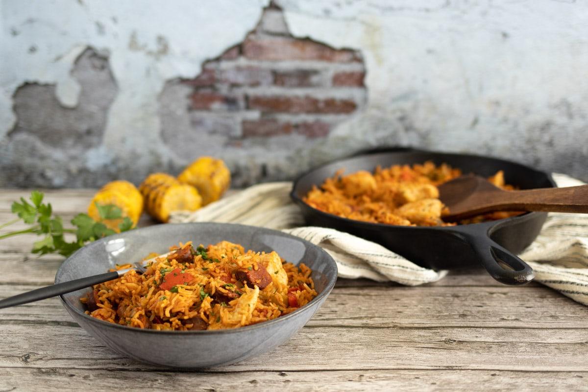 Chicken and chorizo jambalaya in a bowl with a pan behind