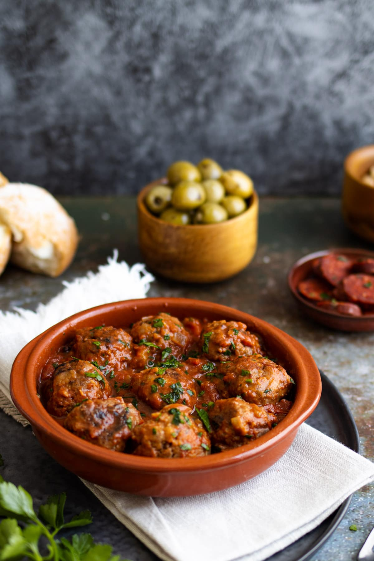 Spanish meatballs in a bowl with cashews and olives