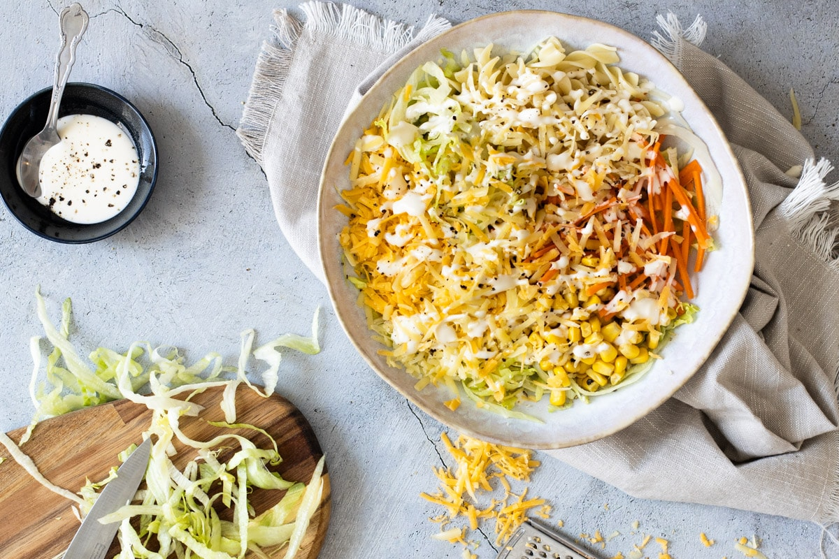 Cheese salad on a plate next to grated cheese and mayo