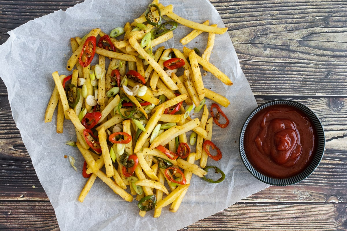 Salt and Pepper Chips on baking paper with ketchup