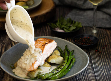 Champagne sauce being poured over salmon