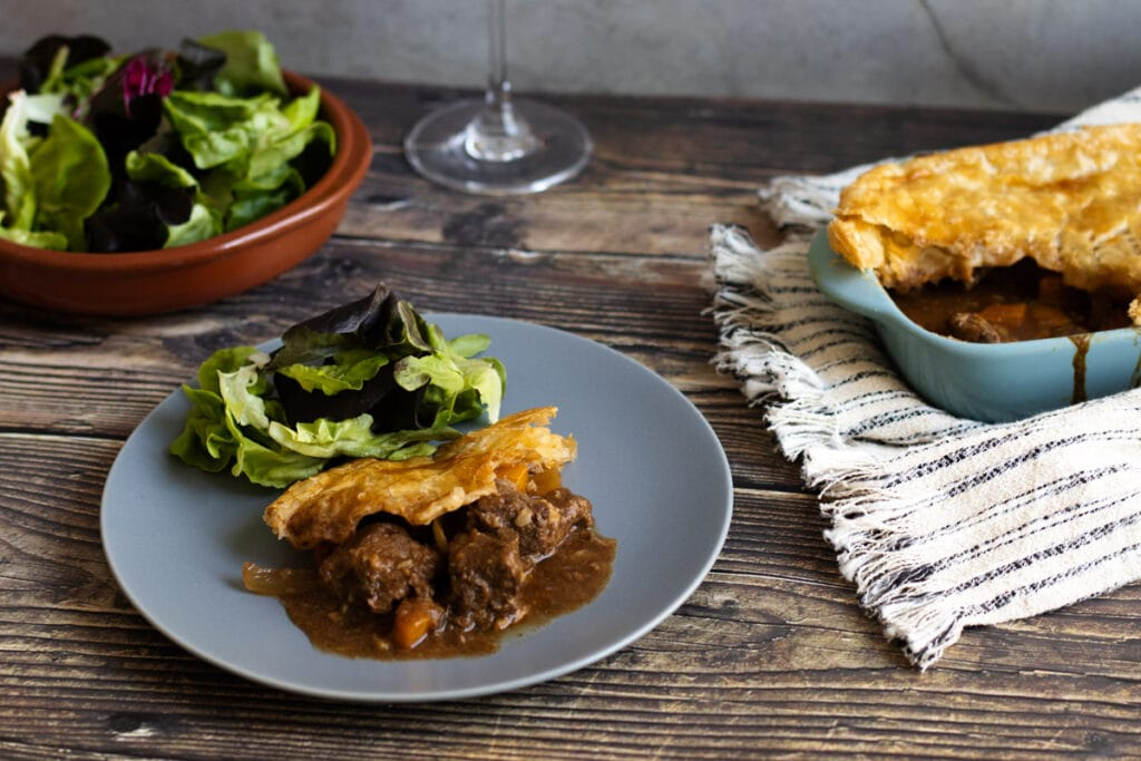 Slow cooker steak pie on a plate with salad in the background