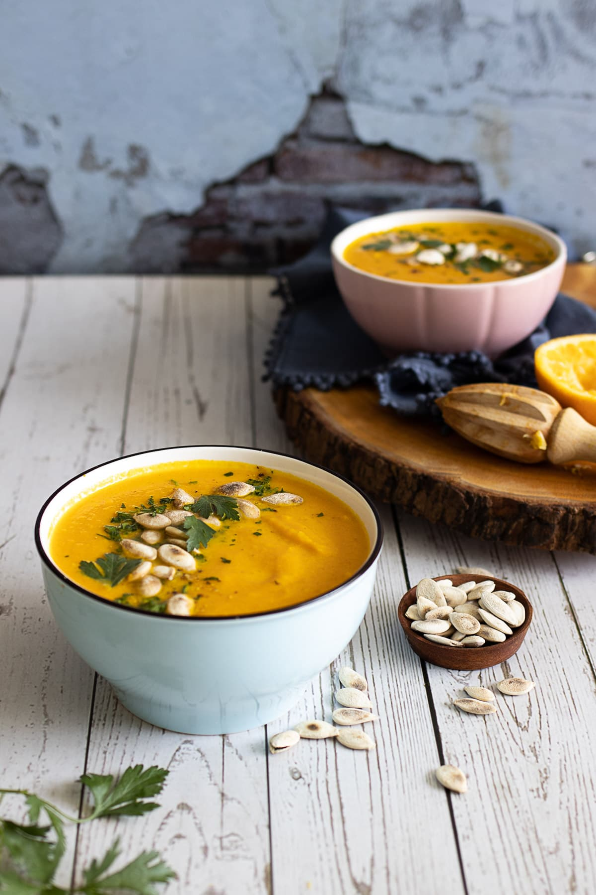 Carrot and orange soup on a table with pumpkin seeds